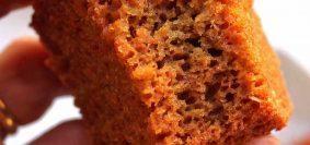 Mão segurando pedaço de bolo de beterraba mordido mostrando bem como o bolo é aerado