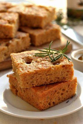 Dois pedaços quadrados de focaccia sobre prato branco, ao fundo um pote de azeite pequeno e vários pedaços cortados de focaccia sobre uma tábua de madeira