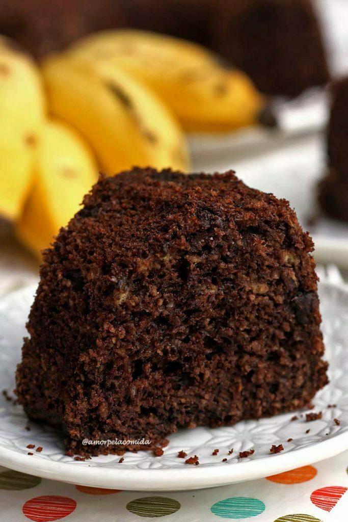 Fatia de bolo de banana com chocolate sobre prato redondo pequeno em uma mesa branca, ao fundo uma penca de banana desfocada e atrás o bolo partido