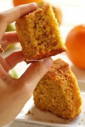 Mão segurando pedaço de bolo de laranja mordido mostrando a textura aerada da massa, abaixo uma fatia de bolo sobre um prato quadrado branco pequeno e laranjas desfocadas sobre uma mesa branca