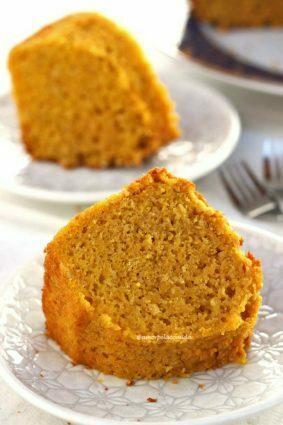Duas fatias de bolo de cenoura com fubá sobre um prato redondo pequeno com detalhes geométricos em uma mesa branca