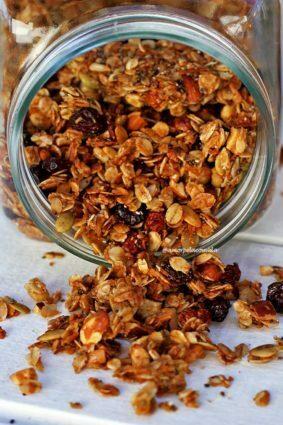Vidro deitado sobre mesa branca, dentro do vidro e saindo dele sobre a mesa granola caseira composta de aveia, sementes, castanhas, coco em flocos e frutas secas