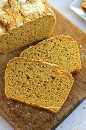 Duas fatias de pão de milho sobrepostas na diagonal sobre uma tábua de madeira, ao lado o pão cortado visto de cima em uma mesa branca