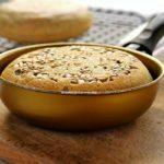 Pão pequeno feito dentro de uma frigideira dourada, no topo do pão sementes de girassol. A frigideira está sobre uma tábua de madeira e ao fundo tem uma grelha preta com mais um pão redondo pequeno de frigideira desfocado da cena principal