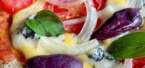 Pizza sobre tábua de madeira, na cobertura queijo, tomate, cebola, manjericão e azeitonas pretas