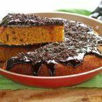 Fatia de bolo de cenoura com cobertura de chocolate sobre uma espátula acima da frigideira com o restante do bolo