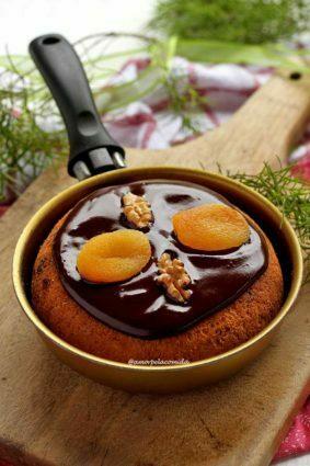 Frigideira pequena dourada sobre tábua de madeira, dentro um panetone decorado com cobertura de chocolate cremosa com damasco e nozes
