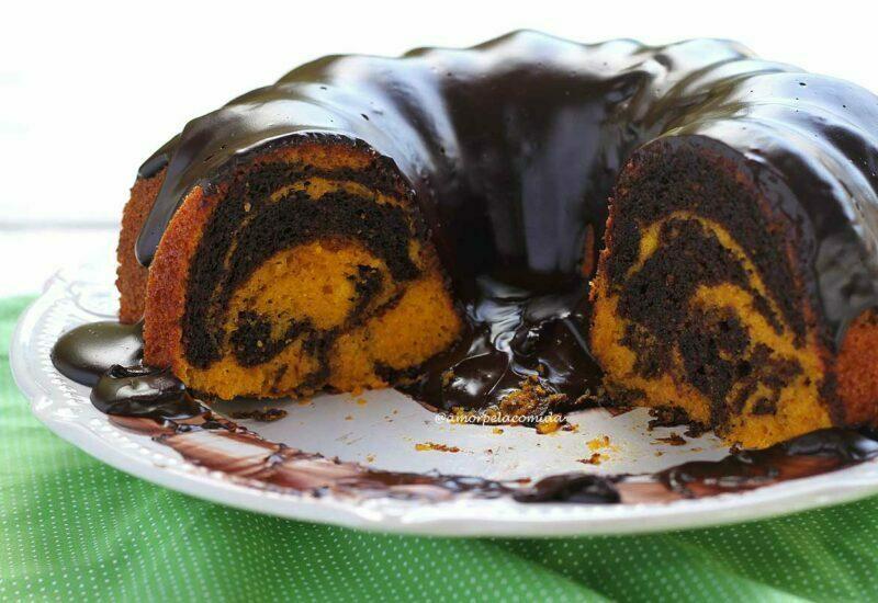 Bolo de cenoura mesclado com chocolate partido sobre prato de bolo branco com cobertura cremosa de chocolate