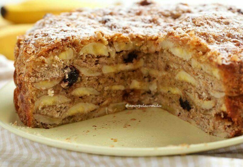 Torta de banana cortada mostrando as camadas internas de banana, algumas passas e a cobertura de aveia com açúcar polvilhado