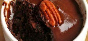 Xícara branca com bolo de chocolate dentro, no topo do bolo uma cobertura de chocolate e uma noz pecan, o bolo já está parcialmente comido