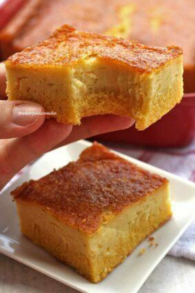 Mão segurando pedaço de bolo de fubá com laranja mordido, abaixo mais uma fatia sobre prato quadrado pequeno, ao fundo uma forma vermelha sobre uma mesa branca