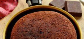 Frigideira dourada com cabo preto com bolo de chocolate dentro