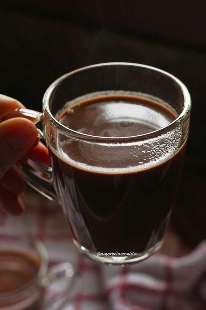 Mão segurando xícara de vidro transparente com chocolate quente dentro