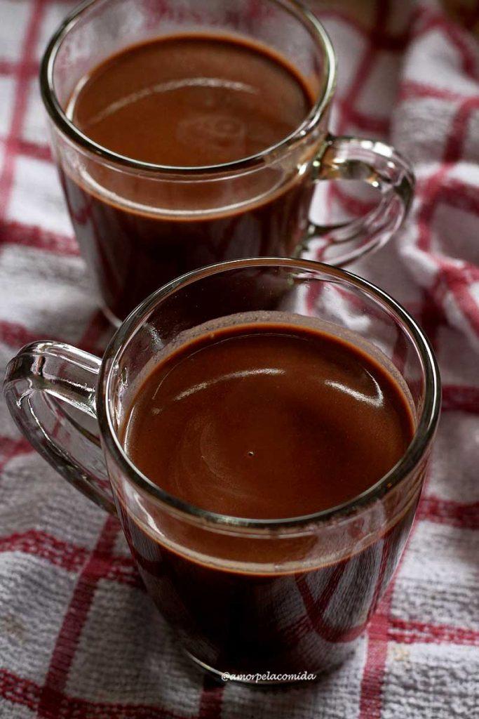 Duas xícaras de chocolate quente sobre pano branco e vermelho quadriculado