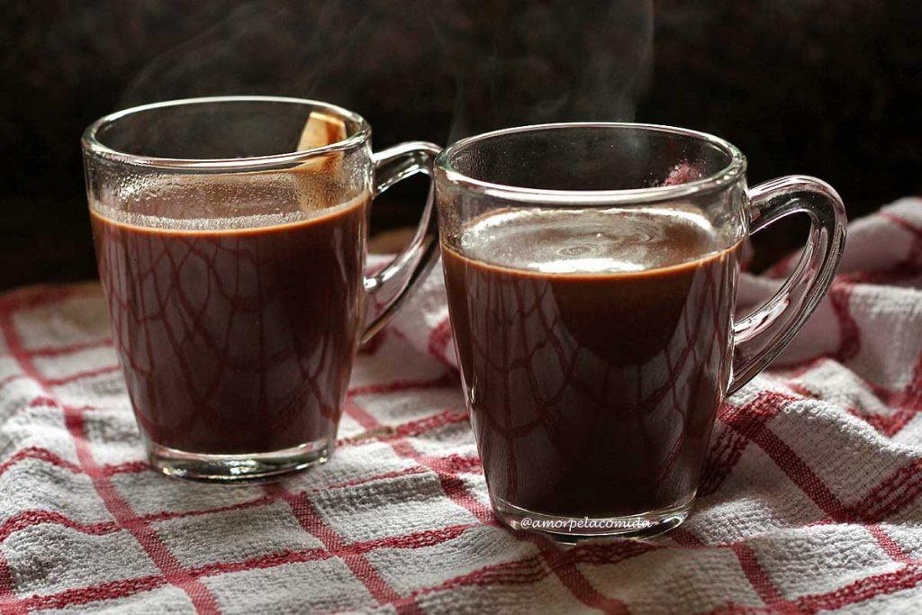 Duas xícaras de chocolate quente sobre pano branco com quadriculado vermelho