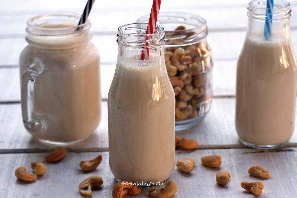 Duas garrafinha e um copo cheios de leite vegetal em uma mesa branca com um vidro de castanha de caju ao fundo