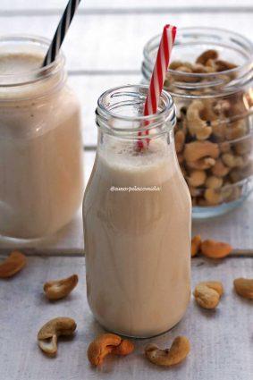 Garafinha de vidro com leite vegetal dentro com canudo vermelho e branco, ao fundo o pote de castanha de caju e mais um copo de leite