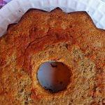 Bolo redondo com furo no meio sobre prato branco, a foto foi tirada de cima para baixo