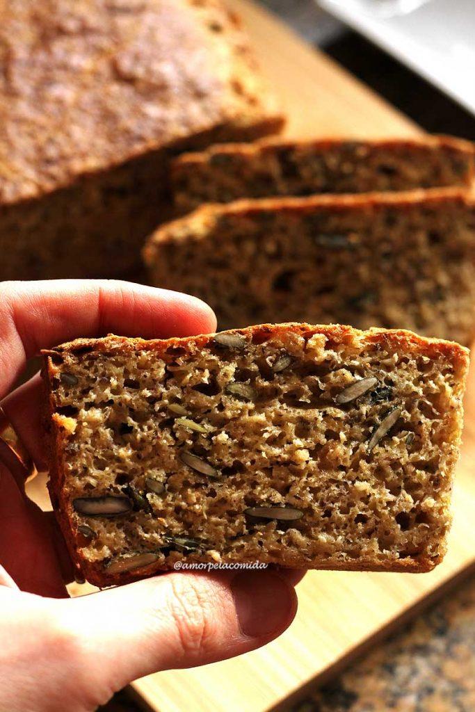 Pão segurando fatia de pão de grão-de-bico, é possível visualizar várias sementes na fatia, ao fundo mais fatias de pão e o pão caseiro desfocado