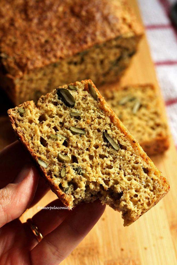 Mão segurando fatia de pão caseiro mordido, abaixo o restante do pão de forma e uma fatia sobreposta em uma tábua de bambu