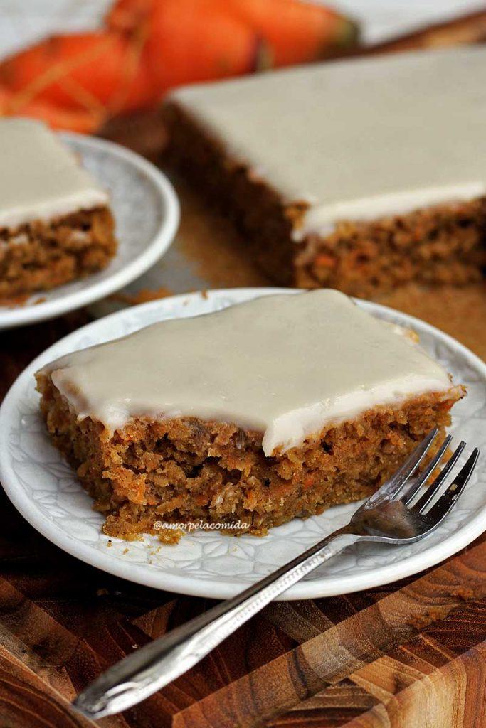 Pedaço de bolo de cenoura com textura rústica e cobertura branca que é cítrica. O bolo está em um prato redondo branco e pequeno ao fundo mais um pedaço de bolo em um prato e o restante do bolo em uma tábua