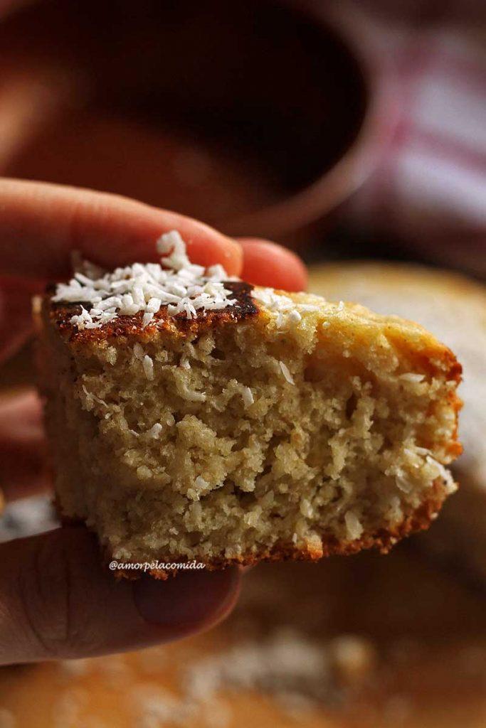 Mão segurando pedaço triangular pequeno de bolo de coco, no topo do bolo alguns flocos de coco