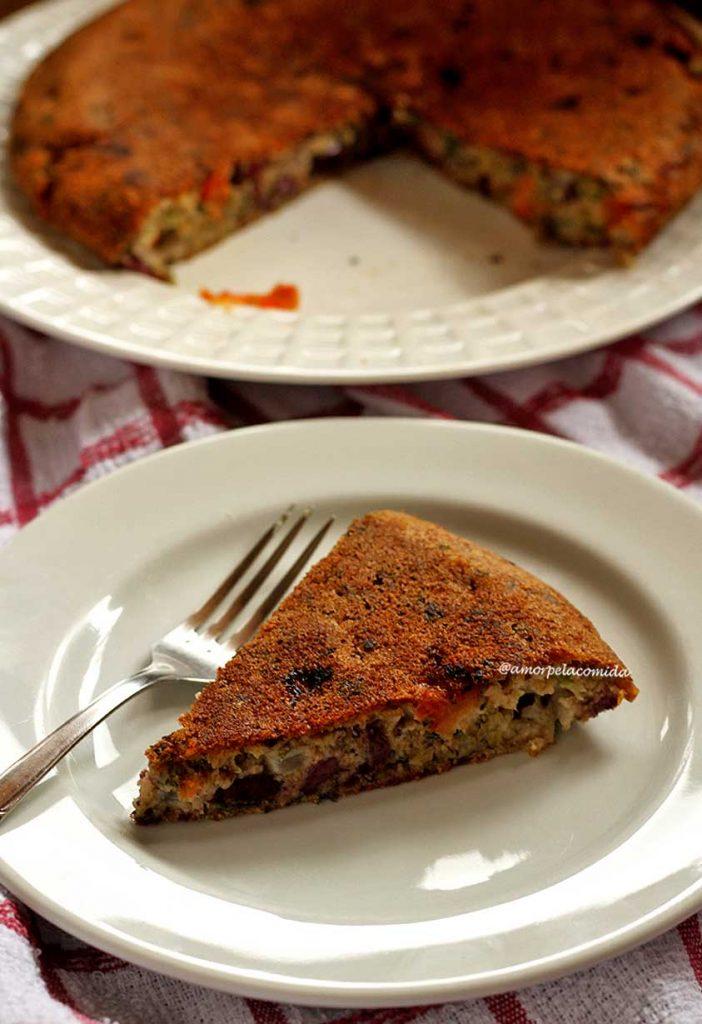 Pedaço triangular de torta de sardinha sobre prato médio redondo branco, ao lado um garfo e ao fundo o restante da torta sobre um prato branco