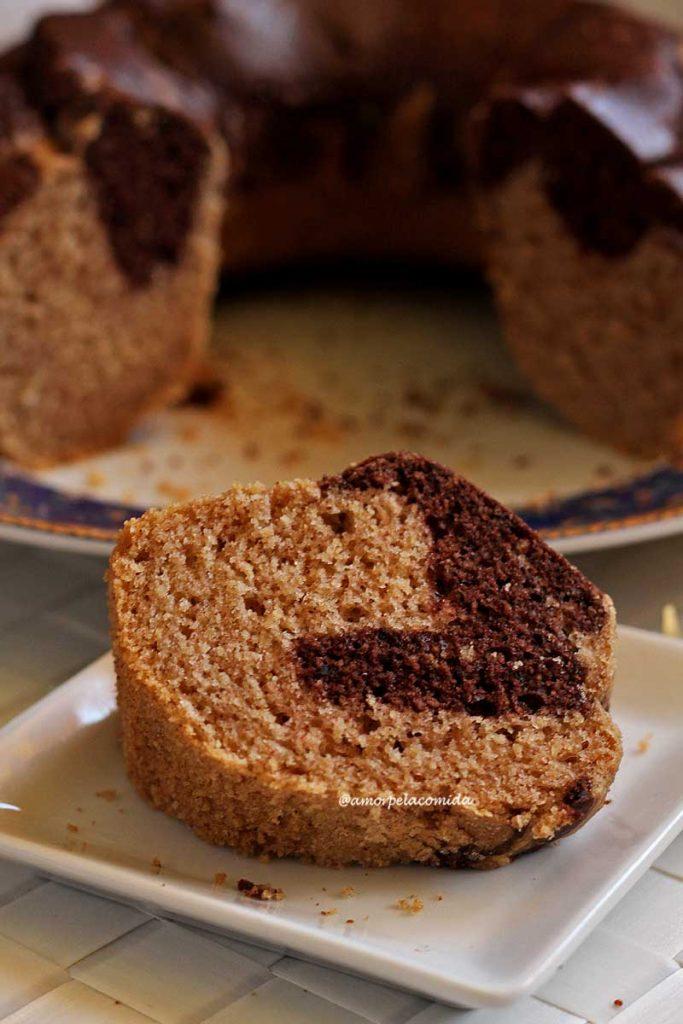 Fatia de bolo de canela com parte mesclada de chocolate sobre prato branco quadrado pequeno, ao fundo o bolo partido