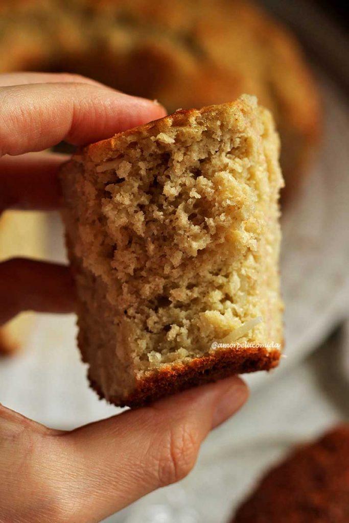 Mão segurando pedaço de bolo mordido mostrando a textura aerada com pedacinhos de coco no meio da massa